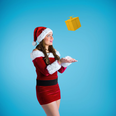 Pretty girl in santa costume holding hand out against blue vignette photo