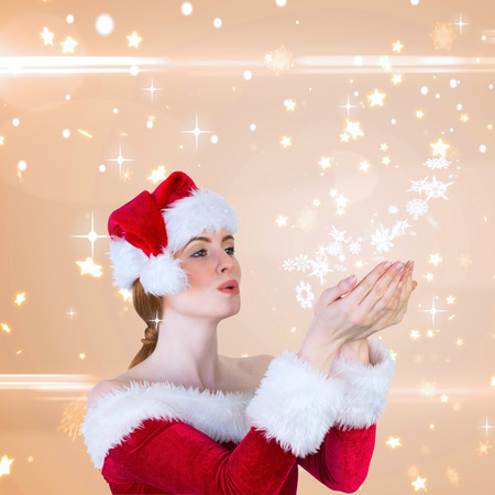 Pretty girl in santa costume holding hand out against bright star pattern on cream photo