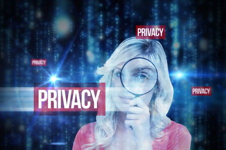 The word privacy and fair-haired woman looking through a magnifying glass against lines of blue blurred letters falling photo