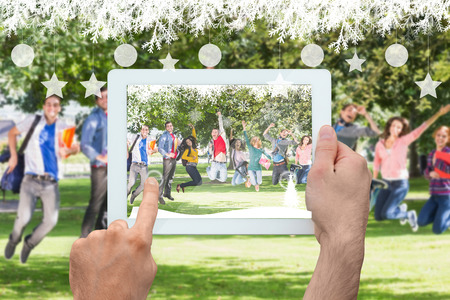 Hand holding tablet pc against college students jumping in the park photo