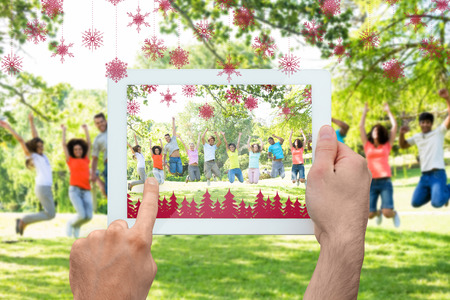 Hand holding tablet pc against cheerful friends jumping photo