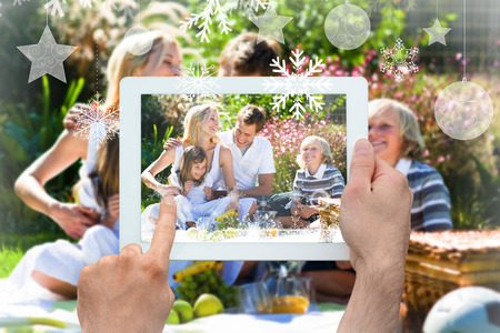 Hands holding tablet pc against happy family playing together in a picnic photo