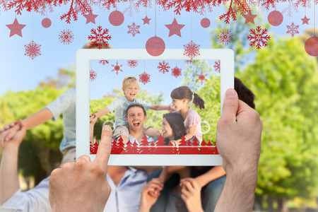 Hands holding tablet pc against parents giving  children a piggyback  photo