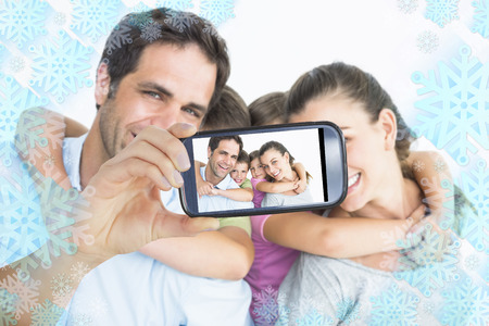 Hand holding smartphone showing smiling young family looking at camera together photo