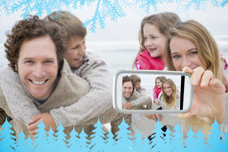 Hand holding smartphone showing happy couple piggybacking kids at beach photo