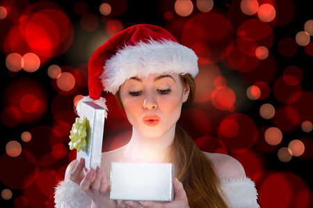 Sexy girl in santa costume opening a gift against red glowing dots on black photo