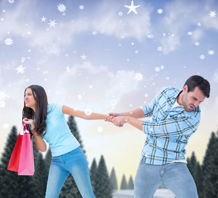 Happy couple with shopping bags against snowy landscape with fir trees photo