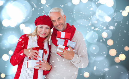 Happy festive couple with gifts against white glowing dots on blue photo