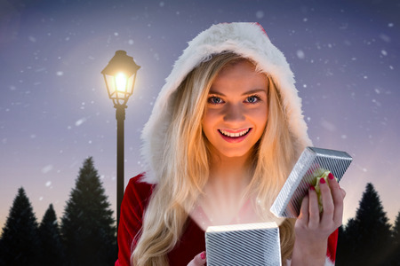 Sexy santa girl opening gift against lamppost at night photo