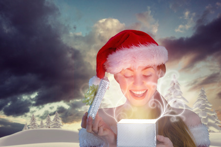 Sexy girl in santa costume opening a gift against snowy landscape with fir trees photo