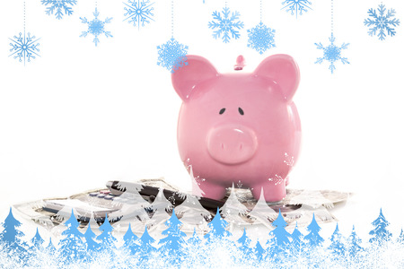 Snowflakes and fir trees against pink piggy bank beside calculator and fountain pen photo