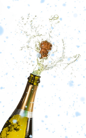 Snow falling against bottle of champagne popping Stock Photo