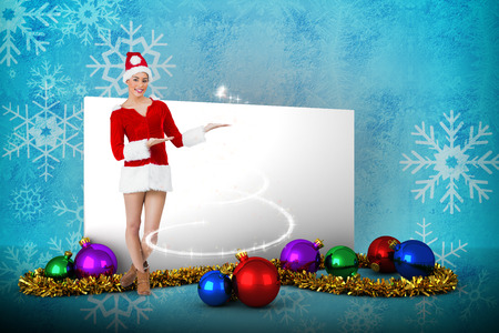 Pretty santa girl presenting with hands against blue snow flake pattern design photo