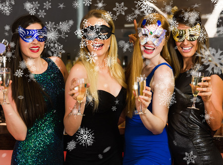 Laughing friends wearing masks holding champagne glasses against snowflakes
