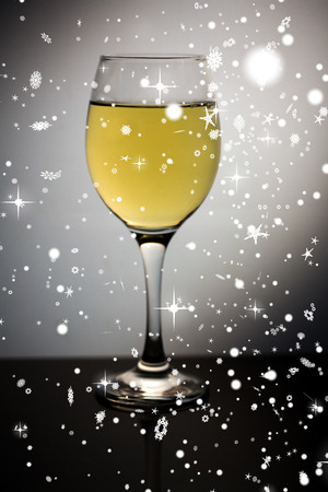 Snow falling against wine glass full of white wine photo