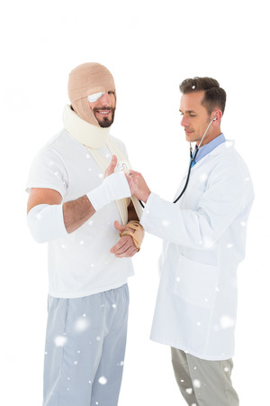 Doctor auscultating patient tied up in bandage with stethoscope against snow falling photo