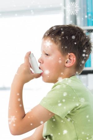 Boy using asthma inhaler in hospital against snow falling photo