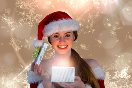 Sexy girl in santa costume opening a gift against cream snow flake pattern design photo
