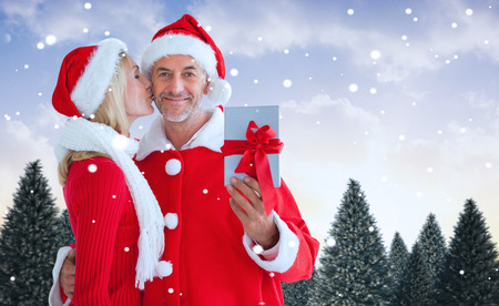 Festive couple against snowy landscape with fir trees photo
