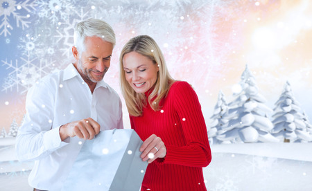 Loving couple with shopping bag against snowy landscape with fir trees photo