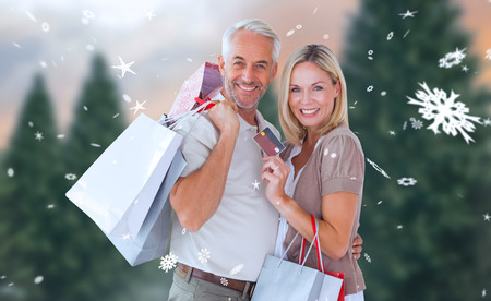 Happy couple with shopping bags and credit card against fir tree forest photo