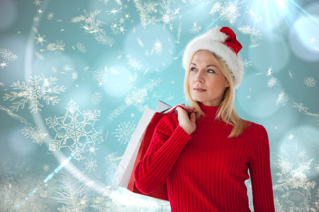 Happy festive blonde with shopping bags against blue snow flake pattern design photo