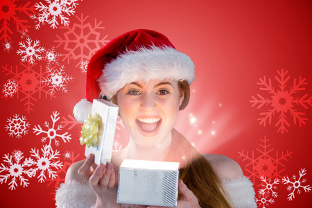 Sexy girl in santa costume opening a gift against red snow flake pattern design photo