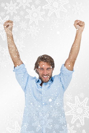 Happy man celebrating success with arms up against snowflakes on silver