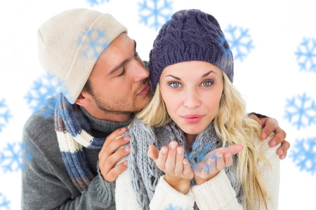 Attractive couple in winter fashion  against snowflakes photo