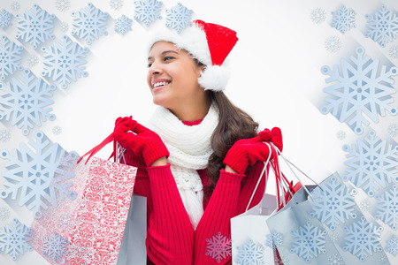 Beautiful festive woman holding shopping bags against snowflake frame photo