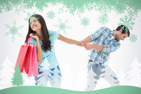 Attractive young man pulling his shopaholic girlfriend against snowflakes and fir tree in green photo