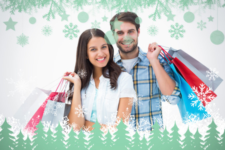 Attractive young couple with shopping bags against snowflakes and fir trees in green photo