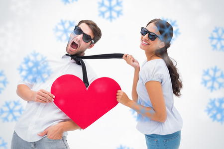 Brunette pulling her boyfriend by the tie holding heart against snowflakes photo