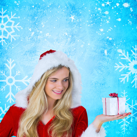 pere noel sexy: Jolie fille � santa tenue tenant cadeau contre la neige bleue conception de mod�le de flocons