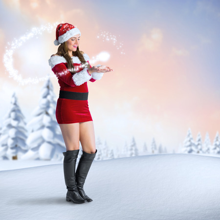 Pretty girl in santa costume holding hand out against snowy landscape with fir trees photo