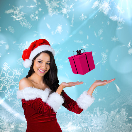 Pretty girl presenting in santa outfit  against blue snow flake pattern design photo
