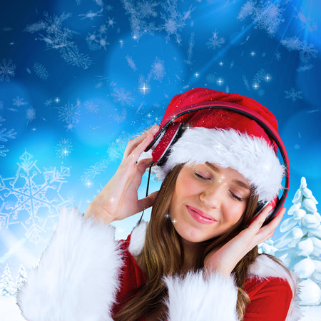 Sexy santa girl listening to music against snowy landscape with fir trees photo