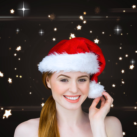 Pretty girl in santa costume smiling at camera against bright star pattern on black