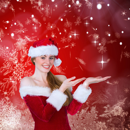 Pretty girl in santa costume holding hand out against red snow flake pattern design photo