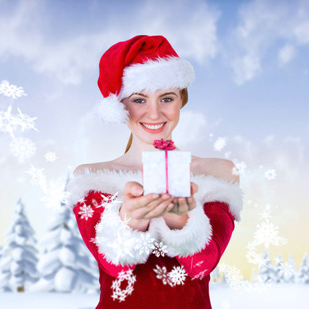 Pretty girl in santa costume holding gift box against snowy landscape with fir trees photo