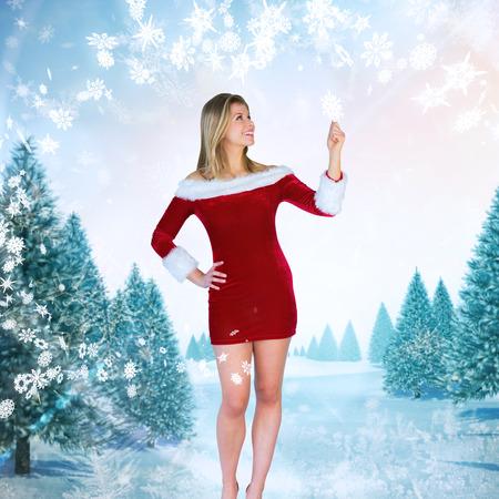 pere noel sexy: Jolie jeune fille souriante � santa tenue contre paysage enneig� avec sapins Banque d'images