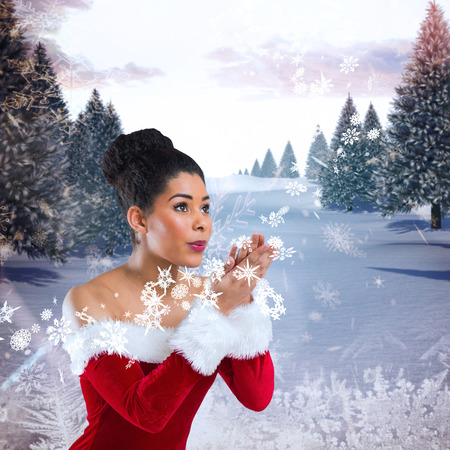 Pretty santa girl blowing over her hands against snowy landscape with fir trees photo