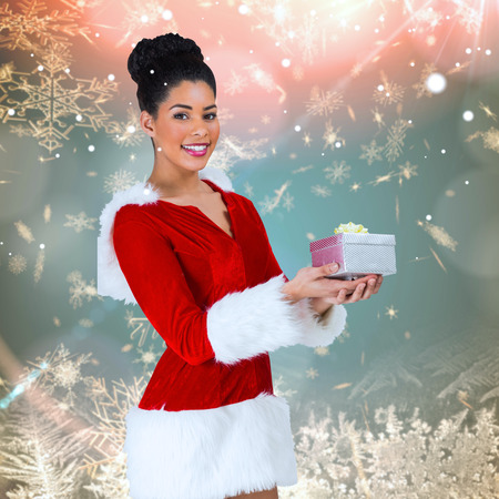 pere noel sexy: Pretty santa girl holding gift against cream snow flake pattern design