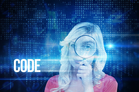 The word code and fair-haired woman looking through a magnifying glass against blue technology interface with binary code photo
