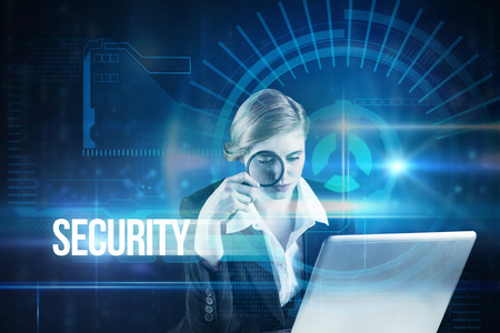 The word security and redhead businesswoman using her laptop against blue technology interface with dial photo