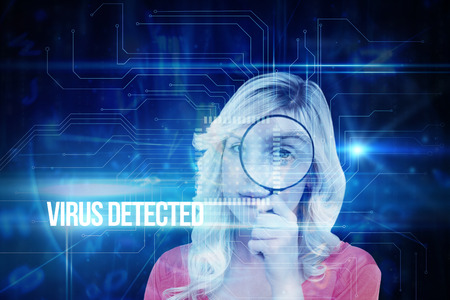 The word virus detected and fair haired woman looking through a magnifying glass against blue technology interface with circuit board photo