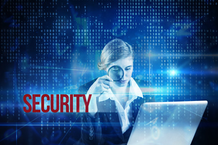 The word security and redhead businesswoman using her laptop against blue technology interface with binary code photo