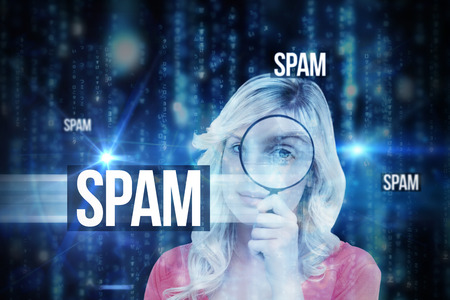The word spam and fair-haired woman looking through a magnifying glass against lines of blue blurred letters falling photo