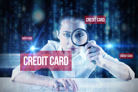 The word credit card and businesswoman typing and looking through magnifying glass against lines of blue blurred letters falling photo