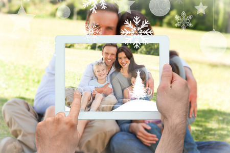 Hands holding tablet pc against family sitting in the park photo